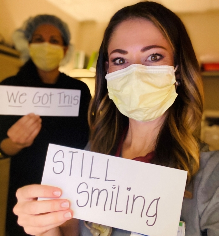 Nurse wearing mask holding a sign that says: Still Smiling.